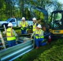 Atmos Energy service technicians wearing yellow vests installing a pipeline