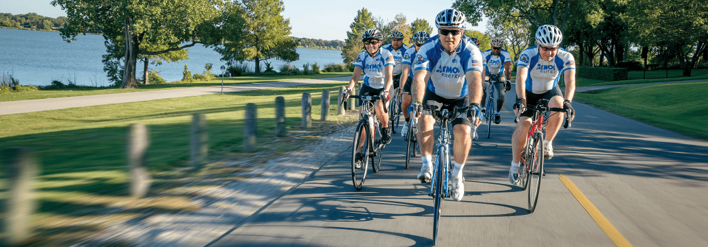 Group of Atmos Energy employees on bikes cycling on paved road with Atmos Energy jerseys.