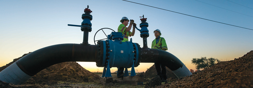 Two Atmos Energy employees working on large pipelines at dusk.
