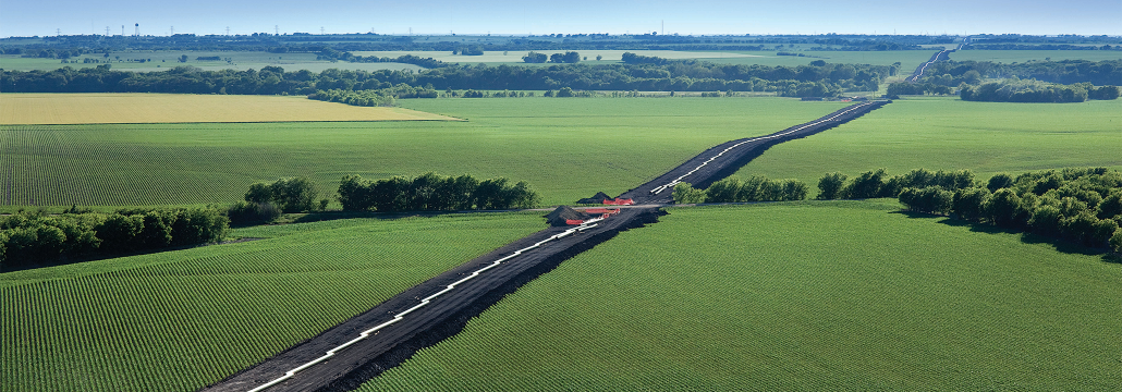 Aerial shot of a long stretch of pipelines in a open green field