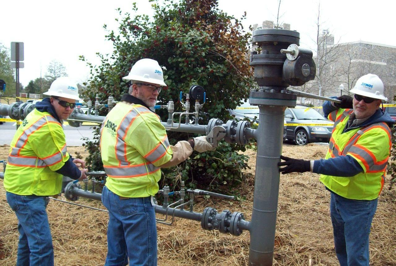 Employees in a yellow vest with a wrench turning a natural gas valve on