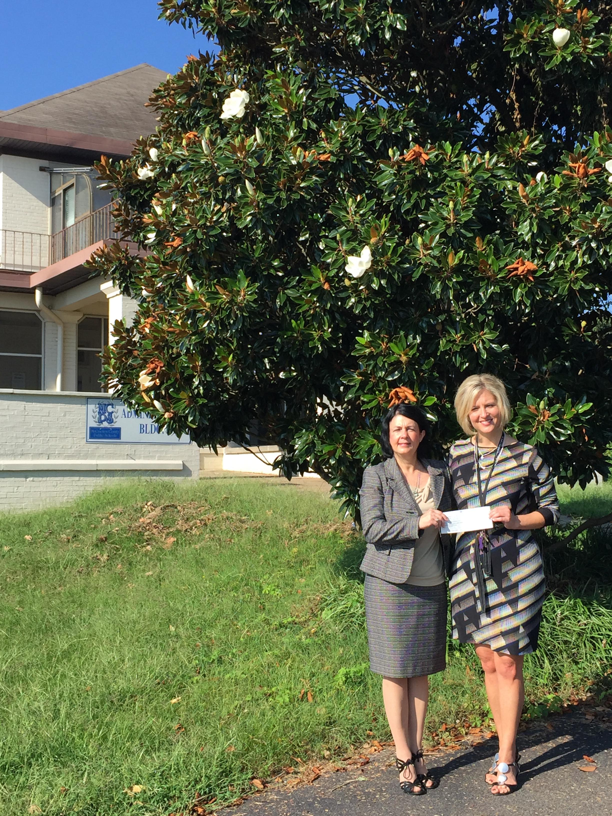 Presenting a contribution from Atmos Energy Corporation to The Merryman House Domestic Crisis Center Executive Director,