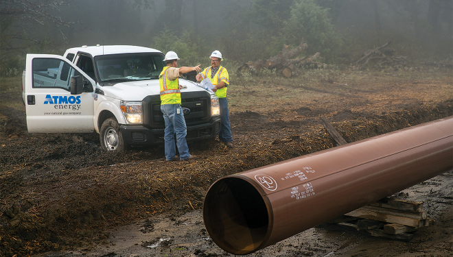 Atmos Energy truck parked in a muddy field with two service inspecting large natural gas pipeline