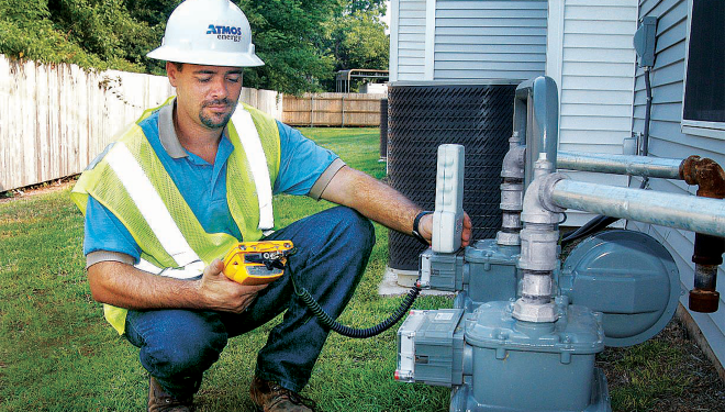 Meter reader at a customer's natural gas meter using a device to measure the customer's gas consumption.